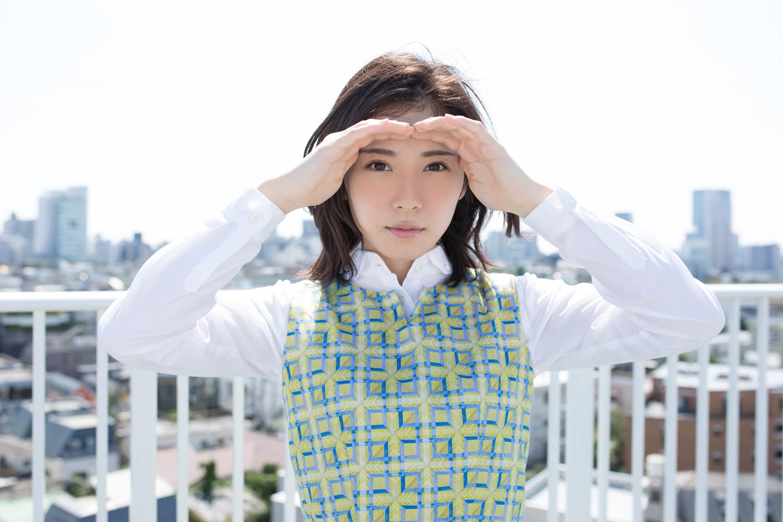 屋上の上で手で日差しをよけて真っ直ぐ見つめる松岡茉優
